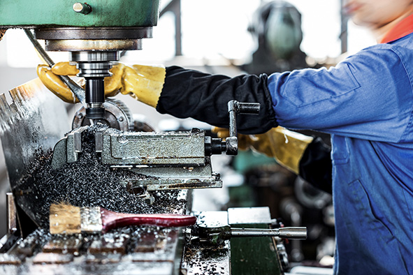 worker operating drilling machine in factory